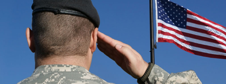 Man in military uniform saluting to American flag